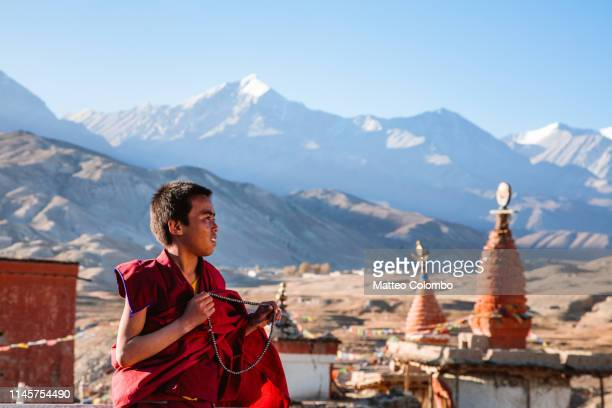 young buddhist monk praying, upper mustang, nepal - lo manthang stock pictures, royalty-free photos & images
