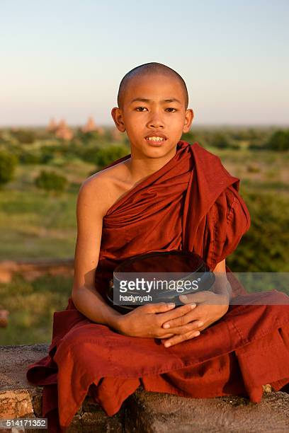 Young Buddhist monk sitting on the roof of temple. Bagan