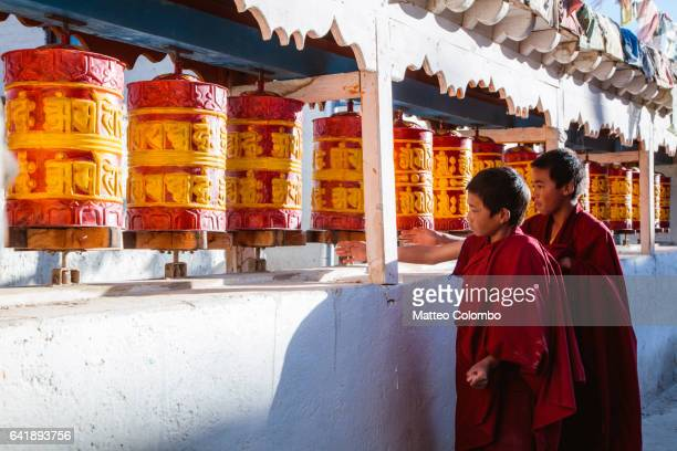 Young buddhist monk spinning prayer wheels, Nepal