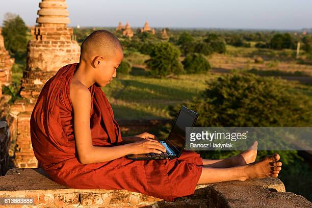 Young Buddhist monk using computer, Bagan on background