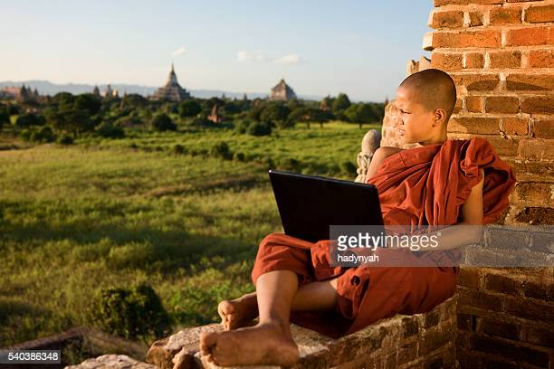 Young Buddhist monk using computer