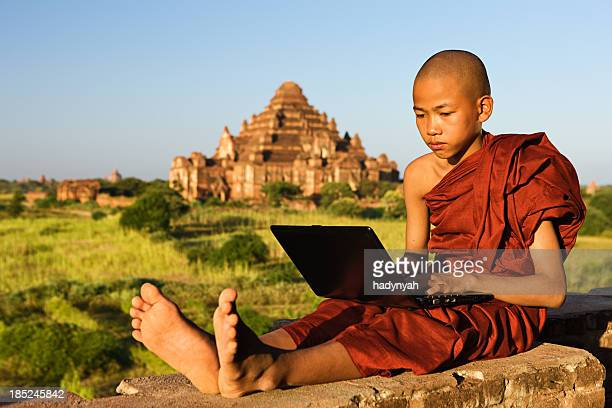 Young Buddhist monk using laptop