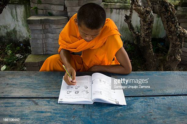 CONTENT] Young Buddhist monk wearing a saffron dress sitting at a blue table on a monastery studying English Luang Prabang Laos