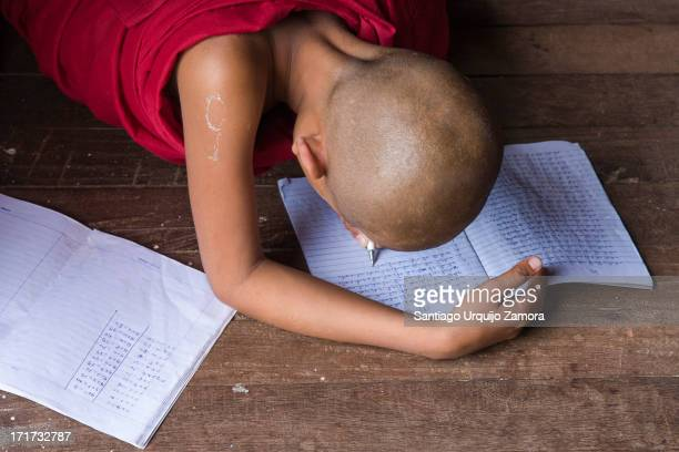 CONTENT] Young Buddhist monk wrapped on a garnet cloak doing his homework on the wooden floor of his monastery Hsipaw Shan State Myanmar