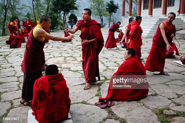 Young buddhist monks at a monastery in Bumthang, central Bhutan, debate what they have learned during their monastic studies. This unique arguing...