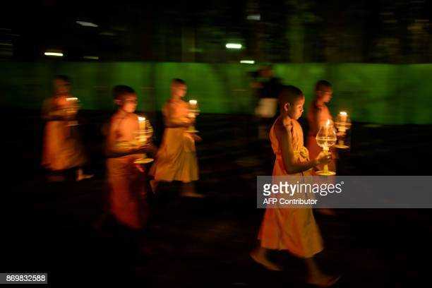 Young Buddhist monks carry lit candles as they participate in a procession around a shrine to Buddha during the celebration of the Yee Peng festival,...