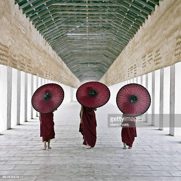 young Buddhist monks walking along temple corridor