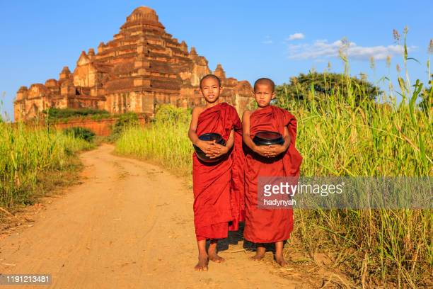 young buddhist monks walking around temples, bagan, myanmar - traditional clothing stock pictures, royalty-free photos & images