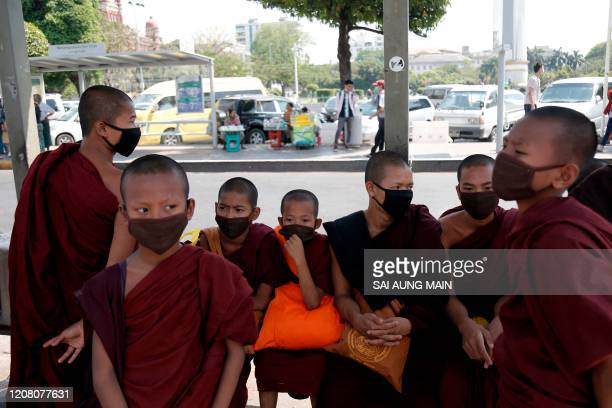 Young Buddhist monks wearing facemasks amid concerns over the spread of the COVID-19 coronavirus look on in Yangon on March 24, 2020. - Myanmar...