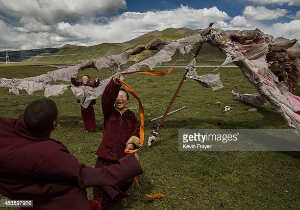 Young Buddhist novice monks play at a Tibetan nomadic summer grazing area on July 24 2015 on the Tibetan Plateau in Yushu County Qinghai China...