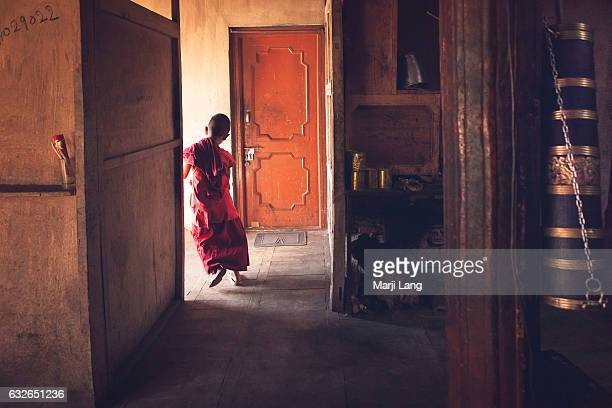 Young Buddhist novice running at the doorstep of the monastery's kitchen in Sumur a little town situated in Nubra valley Ladakh Jammu and Kashmir...
