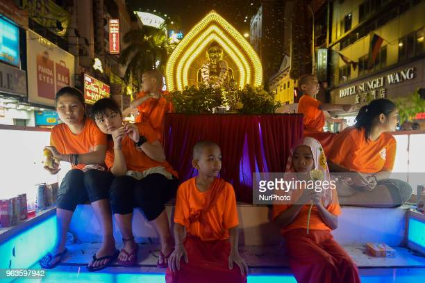 Young buddist mokns and devotees sit on a a colourful float carrying idols of Lord Buddha make their way through the city street during a procession...