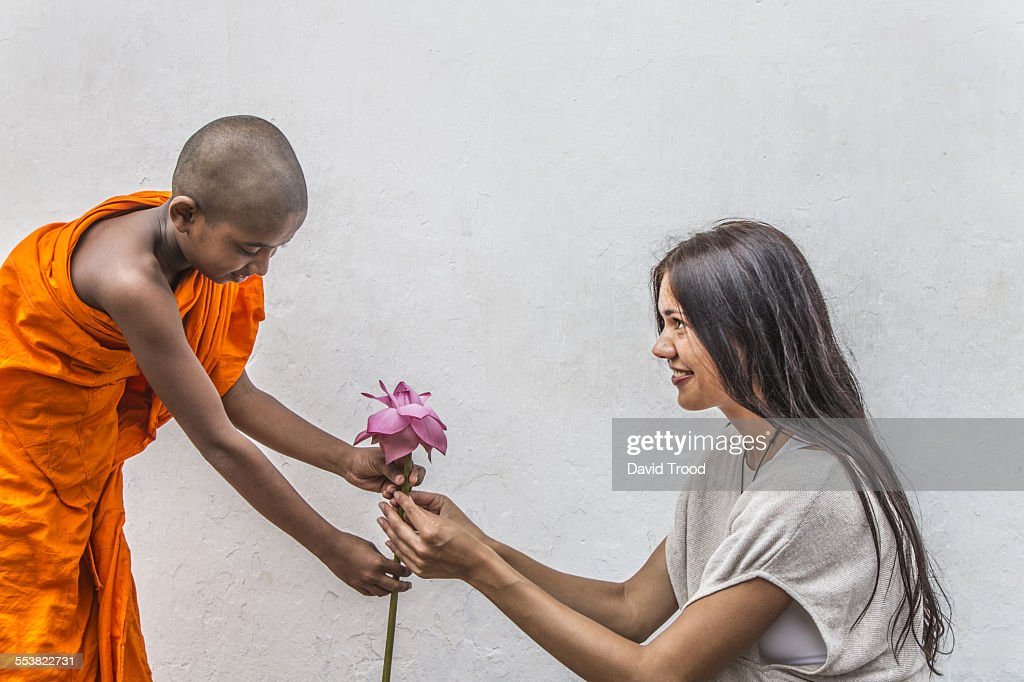 Young Buddist monk gives lotus flower to woman. : Stock Photo