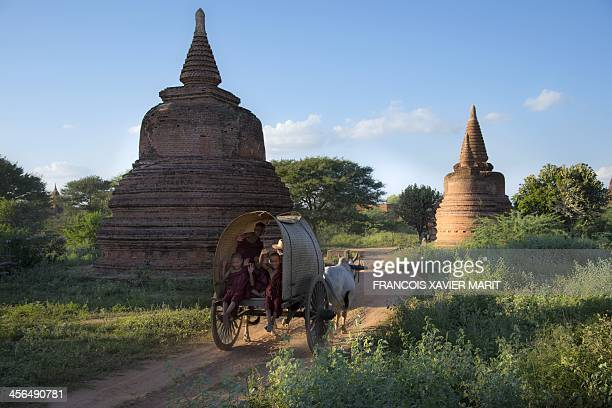 Young Budhist monks wave from an ox cart near a temple on November 30 2013 in Bagan AFP PHOTO / FRANCOIS XAVIER MARIT