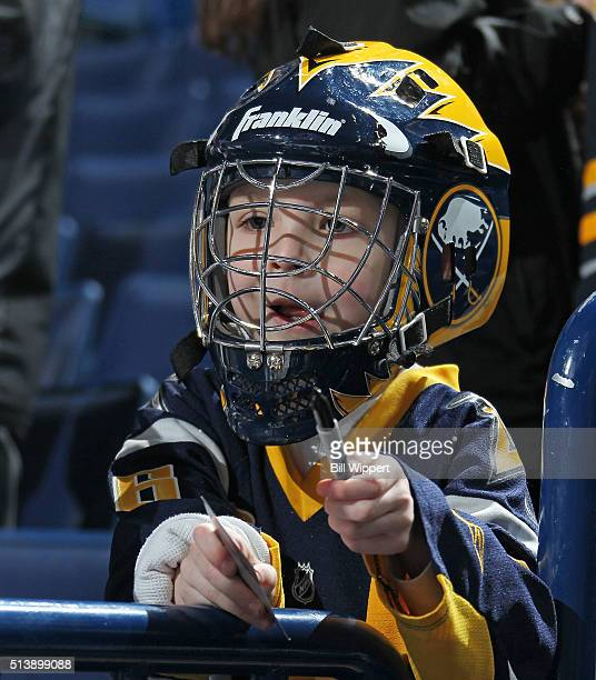 A young Buffalo Sabres fan looks for autographs before their NHL game against the Minnesota Wild on March 5 2016 at the First Niagara Center in...