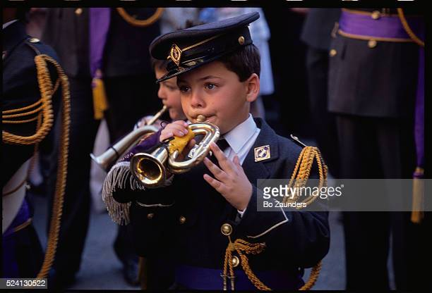 Young bugler wearing a dress uniform performs in a marching band as part of an Easter celebration in Sevilla, Spain.