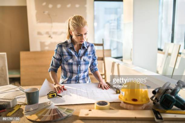 young building contractor examining housing project on construction site. - interior design foto e immagini stock