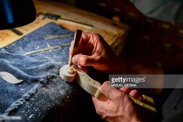 Young Bulgarian luthier, Petar Andreev, carves the scroll of a violin in the workshop of Italian-Colombian Master luthier and president of the...