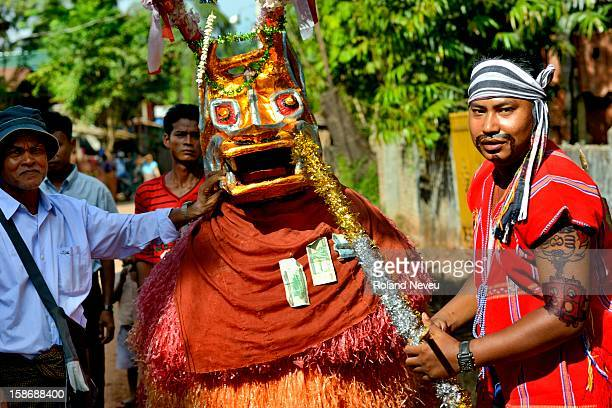 Young Burmese dressed as a bull is entertaining a group of citizen at a neighborhood in Moulmein who have organized a day of festivities to raise...