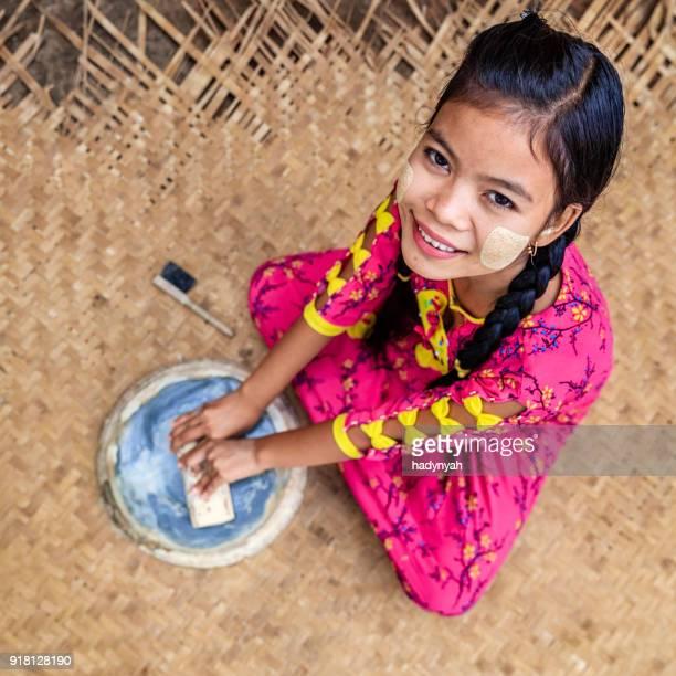 young burmese girl preparing thanaka paste in bagan, myanmar - myanmar stock pictures, royalty-free photos & images