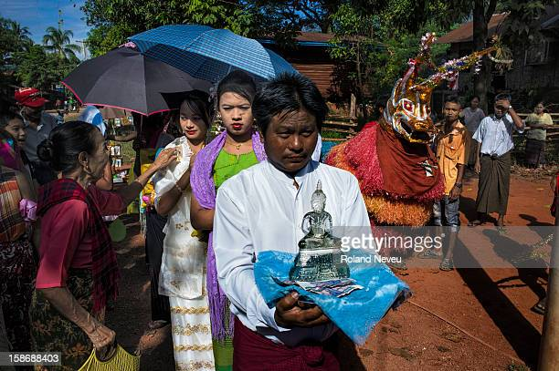 Young Burmese ladies leading the parade of citizen at a neighborhood in Moulmein who have organized a day of festivities to raise money for...