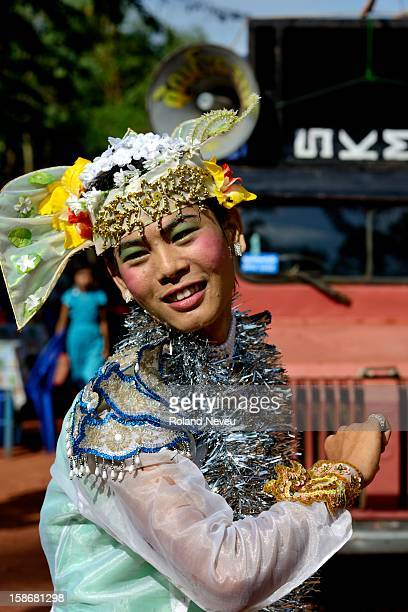 A young Burmese man dressed as a woman is entertaining a group of citizen of a neighborhood of Moulmein who have organized a day of festivities to...