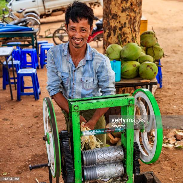 young burmese man making a sugar cane juice in bagan, myanmar - vendor stock pictures, royalty-free photos & images
