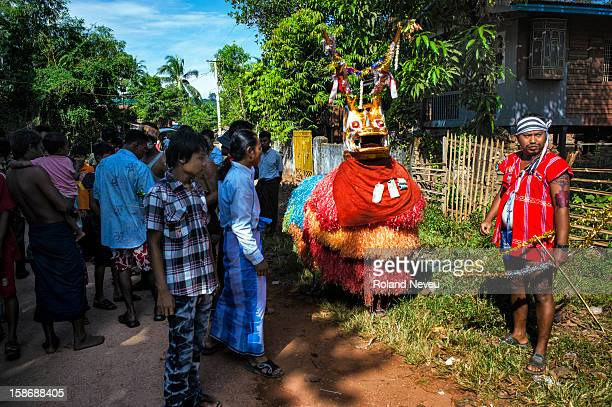 Young Burmese men dressed as a bull is entertaining a group of citizen at a neighborhood in Moulmein who have organized a day of festivities to raise...