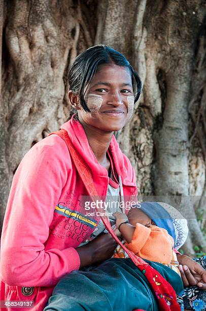 young burmese mother breastfeeding baby - myanmar culture stock photos and pictures