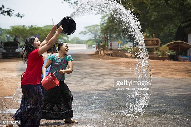Young Burmese women happily throwing buckets of water during Thingyan Water Festival, Myanmar's traditional New Year Festival, in April 2016
