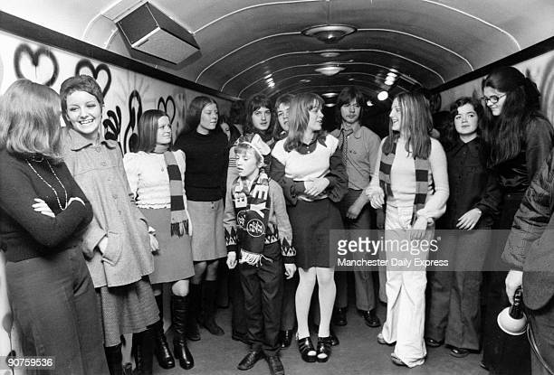 A young Burnley Football Club fan with teenage girls in a train carriage converted into a discotheque with speakers