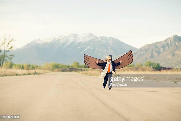 Jovem rapaz de negócios com as asas de cartão voar