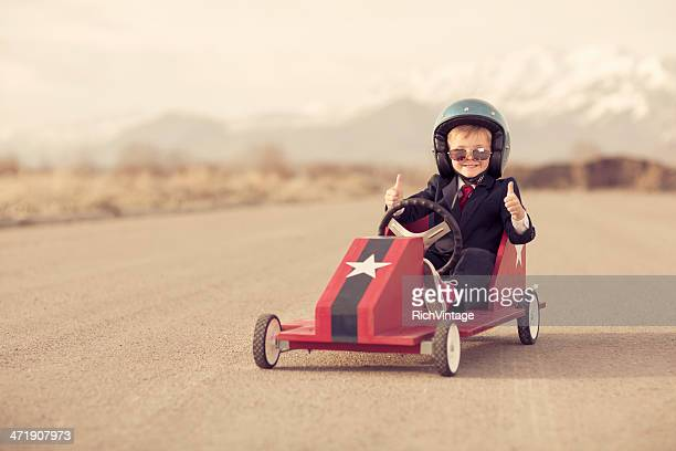 Young Business Boy Giving Thumbs Up Sitting in Toy Car