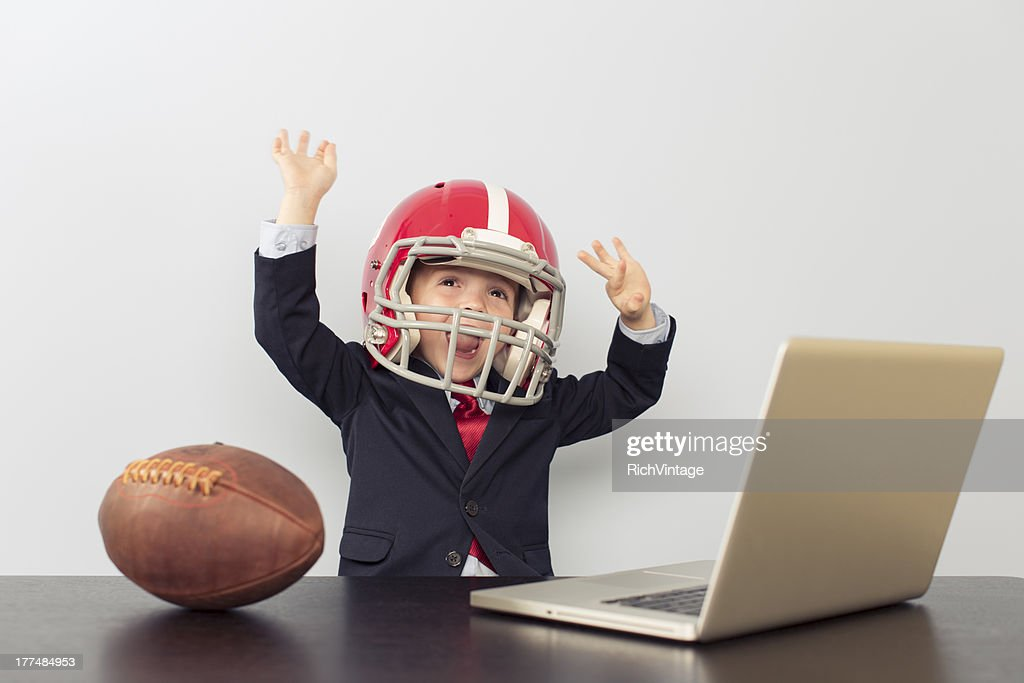 Young Business Boy in Football Helmet at Laptop : Stock Photo