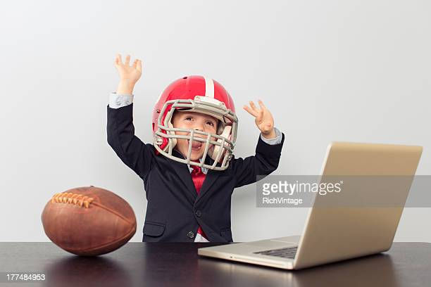 Young Business Boy in Football Helmet at Laptop