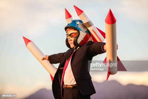young business boy in helmet holding rockets - launch event stock pictures, royalty-free photos & images
