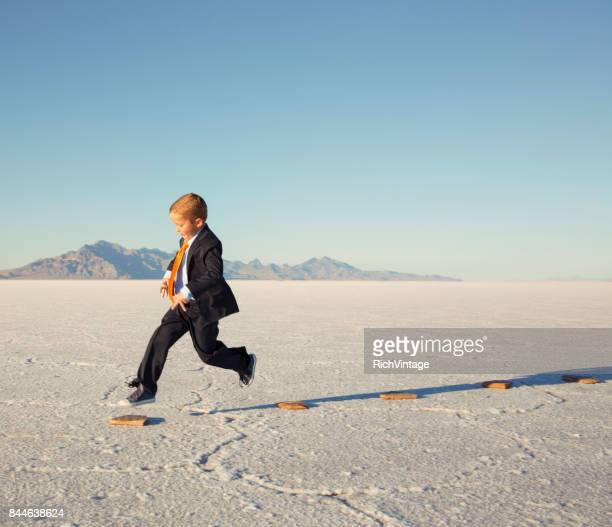 Young Business Boy JumpingOn Stepping Stones