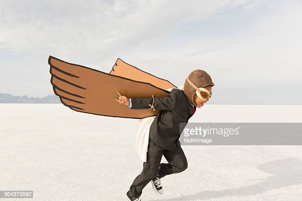 young business boy running with cardboard wings - aircraft wing stock pictures, royalty-free photos & images