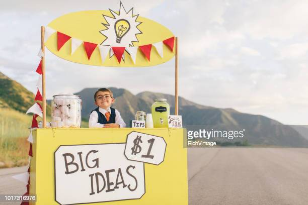 young business boy runs big idea stand - bridging the gap stock photos and pictures
