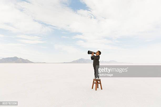 Young Business Boy Standing on Stool Yelling Through Megaphone