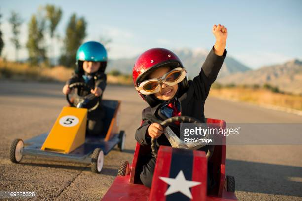 young business boy winning car race - achievement stock pictures, royalty-free photos & images