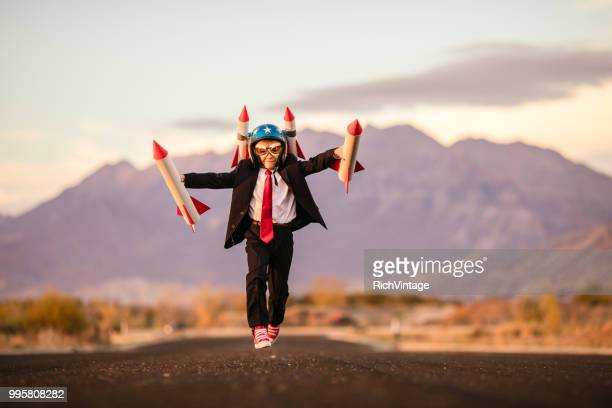 young business boy with rocket helmet - return on investment stock pictures, royalty-free photos & images