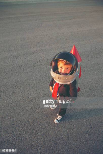 young business boy with rocket on back - launch event stock pictures, royalty-free photos & images