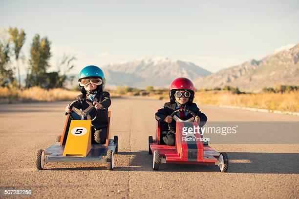 Jeune garçon en costume d'affaires de voitures de course jouet