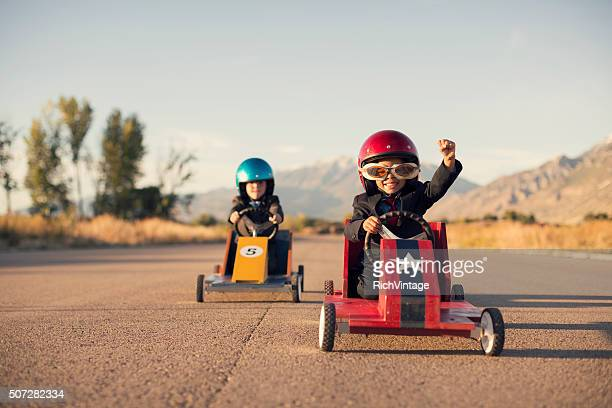 young business boys in suits race toy cars - motivatie stockfoto's en -beelden