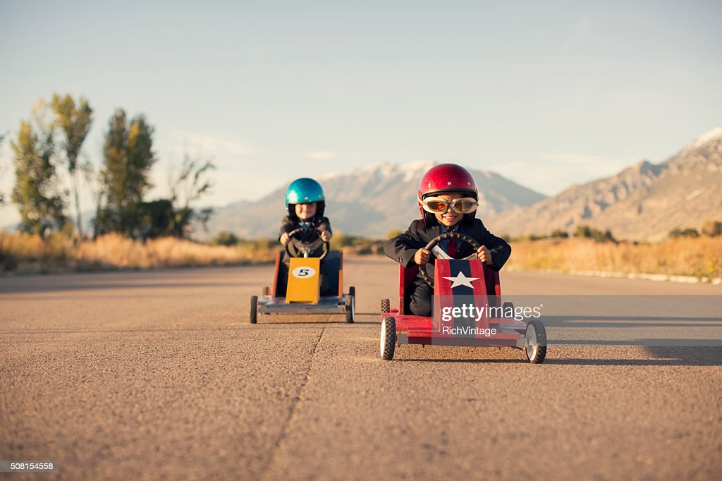 Young Business Boys in Suits Race Toy Cars : Stockfoto