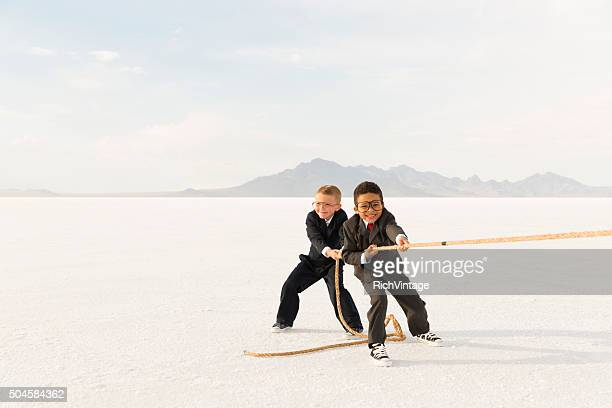 young business boys pulling a tug of war rope - rivalry stock pictures, royalty-free photos & images