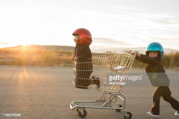young business boys racing a shopping cart - vintage stock stock pictures, royalty-free photos & images