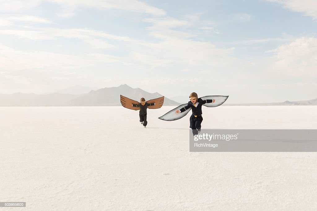 Young Business Boys Wearing Cardboard Wings Are Flying : Stock Photo