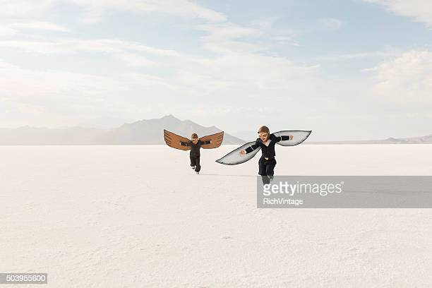 young business boys wearing cardboard wings are flying - rivaliteit stockfoto's en -beelden